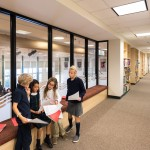 Overlooking the gym are bookcase-lined hallways with meeting spaces for student collaboration.